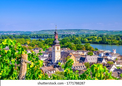 Aerial view of Rudesheim am Rhein historical town centre with clock tower spire of St. Jakobus catholic church and Rhine river, blue sky background, Rhineland-Palatinate and Hesse states, Germany