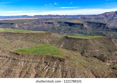 Aerial view of the rugged Arizona landscape after recent rains, topping Black Mesa near Black Canyon City with a surface of green grass