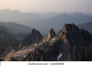 Aerial view of the rugged Canadian Mountain Landscape during a hazy summer evening. Located near Chilliwack, East of Vancouver, BC, Canada.