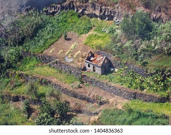an aerial view of a ruined abandoned farmhouse surrounded by walled terraced fields typical of old fashioned small scale agriculture in funchal madeira