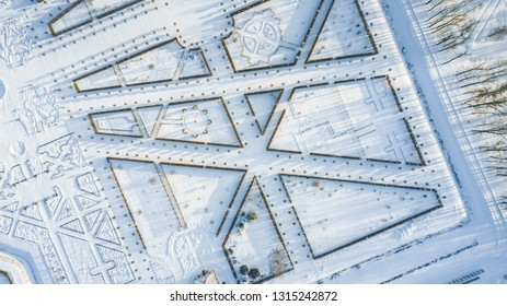 Aerial view of Rundale palace and baroque garden covered in snow at a sunny winter's day. Unique maze type french garden creates symmetrical view with different type of shapes.