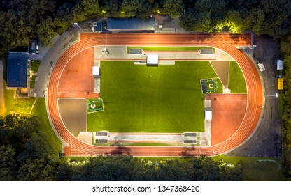 Aerial view of running track where athletics are training at night under bright stadium lights