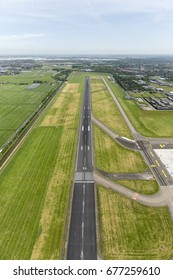 Aerial view of the runway of an airport near the city of Rotterdam on a clear day with a beautiful horizon.