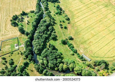 aerial view of rural area with farm fields and winding small river among green trees in sunny summer day
