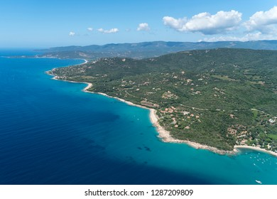 Aerial view of a rural beach at the french island Corsica in the Mediterranean Sea. A beautiful coast for snorkling, swimming and enjoying nature. The ocean water is crystal clear and azure blue.