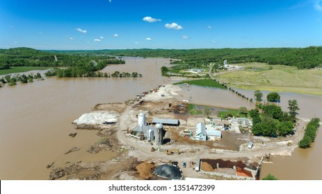 Aerial View of Rural Farm affected by Spring flooding featuring Farm house, silo on dry ground surrounded by flooded fields