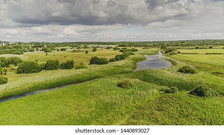 Aerial view rural landscape, green pasture, river, blue cloudy sky, sunny day, county Galway.