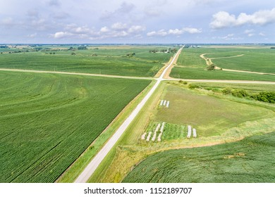aerial view of rural Nebraska landscape with a farm road, soybean field and hay bales