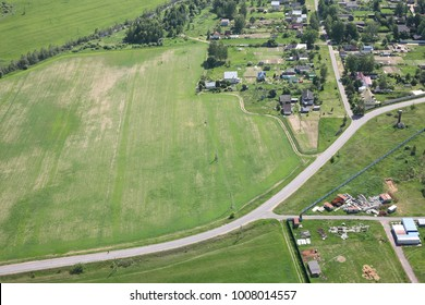 Aerial View - Russian village at the road and building, meadows and fields. Shooting from the helicopter.