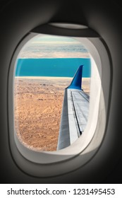 Aerial view of the Sahara desert and the Red Sea (Gulf of Suez) and the wing of a commercial airplane photographed through the porthole window. Egypt, Africa.