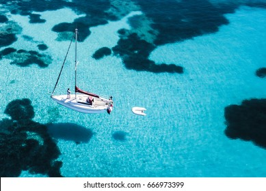Aerial view of a sail boat in front of Mortorio island in Sardinia. Amazing beach with a turquoise and transparent sea. Emerald Coast, Sardinia, Italy.