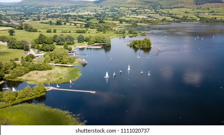 Aerial view of sailing boats on a large lake surrounded by farmland (Llangorse Lake, Wales)