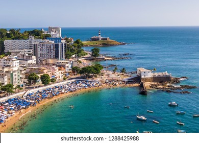 Aerial view of Salvador da Bahia, Brazil, showing Porto da Barra Beach and historical landmarks Barra Lighthouse and Santa Maria Fort during summer.