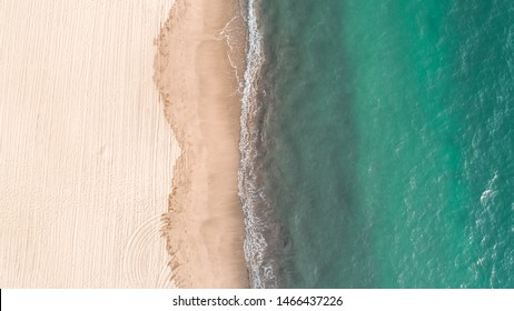 Aerial view. Sand beach aerial, top view of a beautiful sandy beach aerial shot with the blue waves rolling into the shore. Top view of beautiful white sand beach with turquoise sea water.