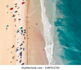 Aerial view of a sandy beach with beachgoers and their umbrellas