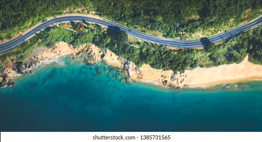 Aerial view of the sandy beach and curved asphalt road