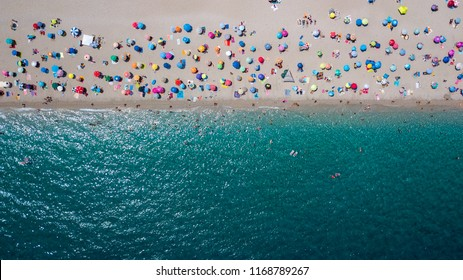 Aerial view of a sandy beach line full of bathers and colorful umbrellas