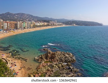 Aerial view of sandy beach with sea, hotels and unrecognizable people in Lloret de Mar, Catalonia, Spain