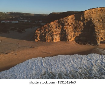Aerial view from a sandy beach at the sunset with an amazing cliff. Drone photo