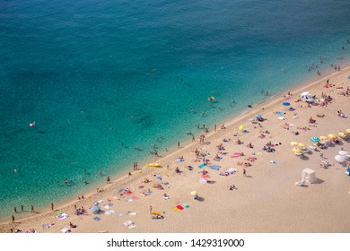 Aerial view of sandy beach with tourists swimming in beautiful clear sea water. People bathing in the sun, swimming and playing games on the beach. Tourists. Sea. Beach. Summer. Vacation. Vacation.