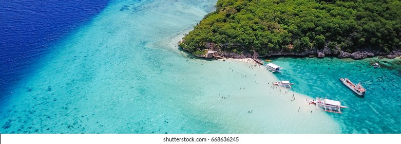 Aerial view of sandy beach with tourists swimming in beautiful clear sea water of the Sumilon island beach landing near Oslob, Cebu, Philippines. - Boost up color Processing. Panoramic banner.