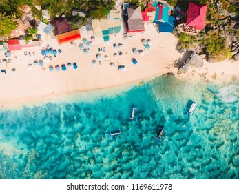 Aerial view of sandy beach with turquoise sea water and local tradition boats, drone shot