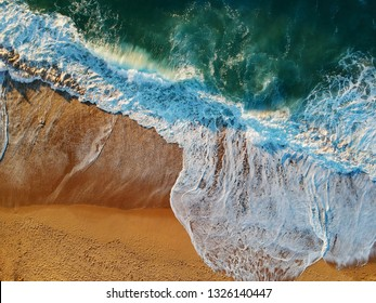 Aerial view of sandy beach with waves and clear ocean water. Drone phot