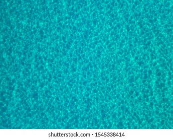 Aerial view of a sandy seabed, crystal clear blue water, reflections of the sun cause ripples on the sea surface. Texture and background. Pool