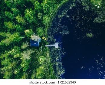 Vue aérienne du Sauna house au bord du lac. Forêt verte et lac bleu en Finlande. Passerelle en bois avec bateau de pêche.
