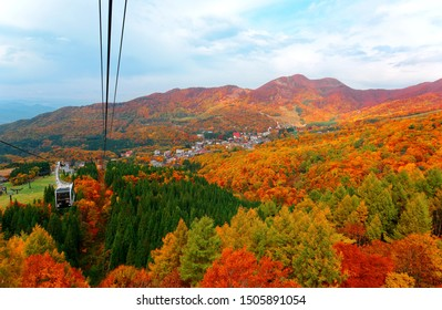 Aerial view of a scenic cable car flying over the beautiful autumn valley of Zao, a famous resort for skiing and Onsen ( hot springs) in Yamagata, Japan, with brilliant fall colors on the mountainside