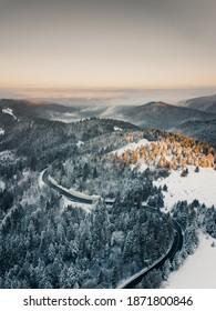 Vista aérea de una pintoresca autopista que pasa por el paisaje montañoso de los Cárpatos durante un colorido amanecer de invierno.