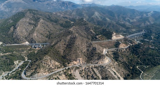 Aerial view of scenic mountain road in the Spanish mountains. Highway A7 leads from Malaga in the direction of Sierra Nevada in a beautiful landscape. Sierra Nevada is visible in the right top corner