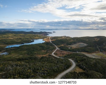 Aerial view of a scenic road on a rocky Atlantic Ocean Coast during a cloudy sunset. Taken in Twillingate, Newfoundland, Canada.