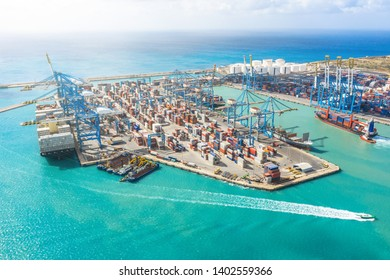 Aerial view of the sea cargo port with a huge number of containers, cranes for unloading goods. Large ship at the pier at unloading. Maritime transport concept