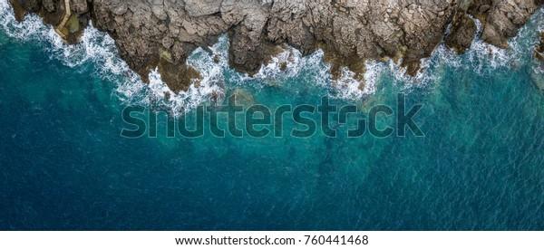 Вид с воздуха на морские волны и фантастический скалистый берег, Черногория