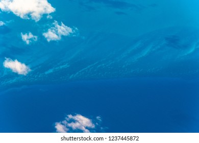 Aerial view of the seabed in the Atlantic Ocean. Point of view from a plane flying over the East coast of Florida, USA. The seabed has diverse tonalities of blue depending on the depth of the water