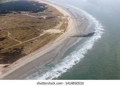 Aerial view seaside Dutch island Ameland with beach, lighthouse and holiday homes in the dunes