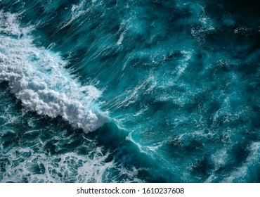 Aerial view to seething waves with foam. Blue water background. Dramatic colors photo.