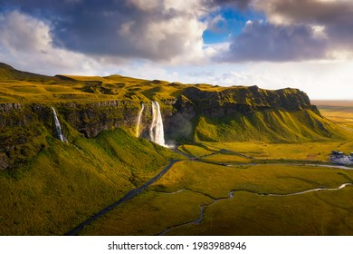 Aerial view of Seljalandsfoss Waterfall, Seljalands River, waterfall parking and the ring road in Iceland at sunset.