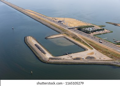 Aerial view service harbor along Dutch dike Afsluitdijk, separation between the fresh water lake IJsselmeer and the salt Wadden Sea