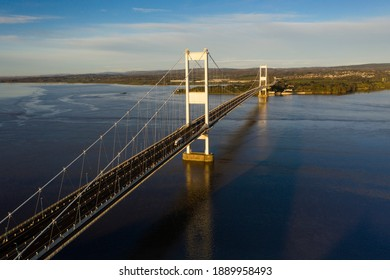 Aerial view of the Severn Bridge in the morning sun, casting a shadow of the motorway into the estuary.