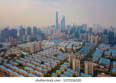 Aerial view of Shanghai Downtown, China. Financial district and business centers in smart city in Asia with residential houses. Top view of skyscraper and high-rise buildings at noon.