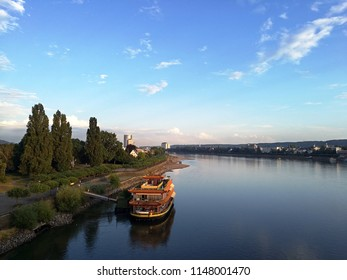 Aerial view of a ship sailing through the river against vegetation and cityscape