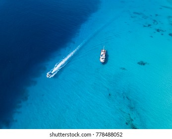 Aerial view of ship and speedboat in the crystal clear waters of the Turks and Caicos.