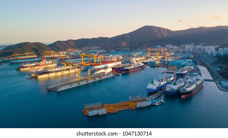 Aerial view of shipyard in the bay. Image consist of many commercial ship, platform, floating dock and large crane.