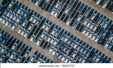 Aerial view shot from drone of a car distribution centre, new cars parked in rows on a lot ready for import export business.