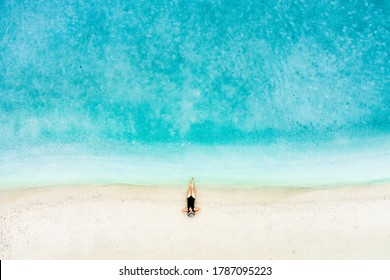 Aerial view shot of the woman sleep on the beach with turquoise sea water with copy space, holiday concept