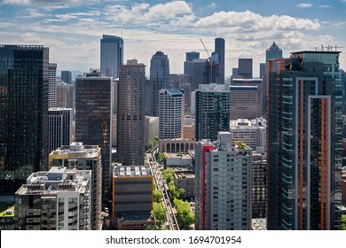 An aerial view shows Fifth Avenue curving below the modern architecture of the Seattle, Washington skyline on a sunny, summer afternoon
