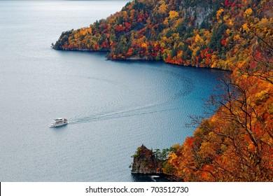 Aerial view of a sightseeing boat cruising on Lake Towada in beautiful autumn season, in Towada Hachimantai National Park, Aomori, Japan ~ Breathtaking scenery of grand nature in Northeastern Japan