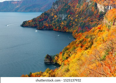 Aerial view of sightseeing boats cruising on Lake Towada with beautiful foliage in autumn, in Towada Hachimantai National Park, Aomori, Japan~Breathtaking scenery of grand nature in Northeastern Japan